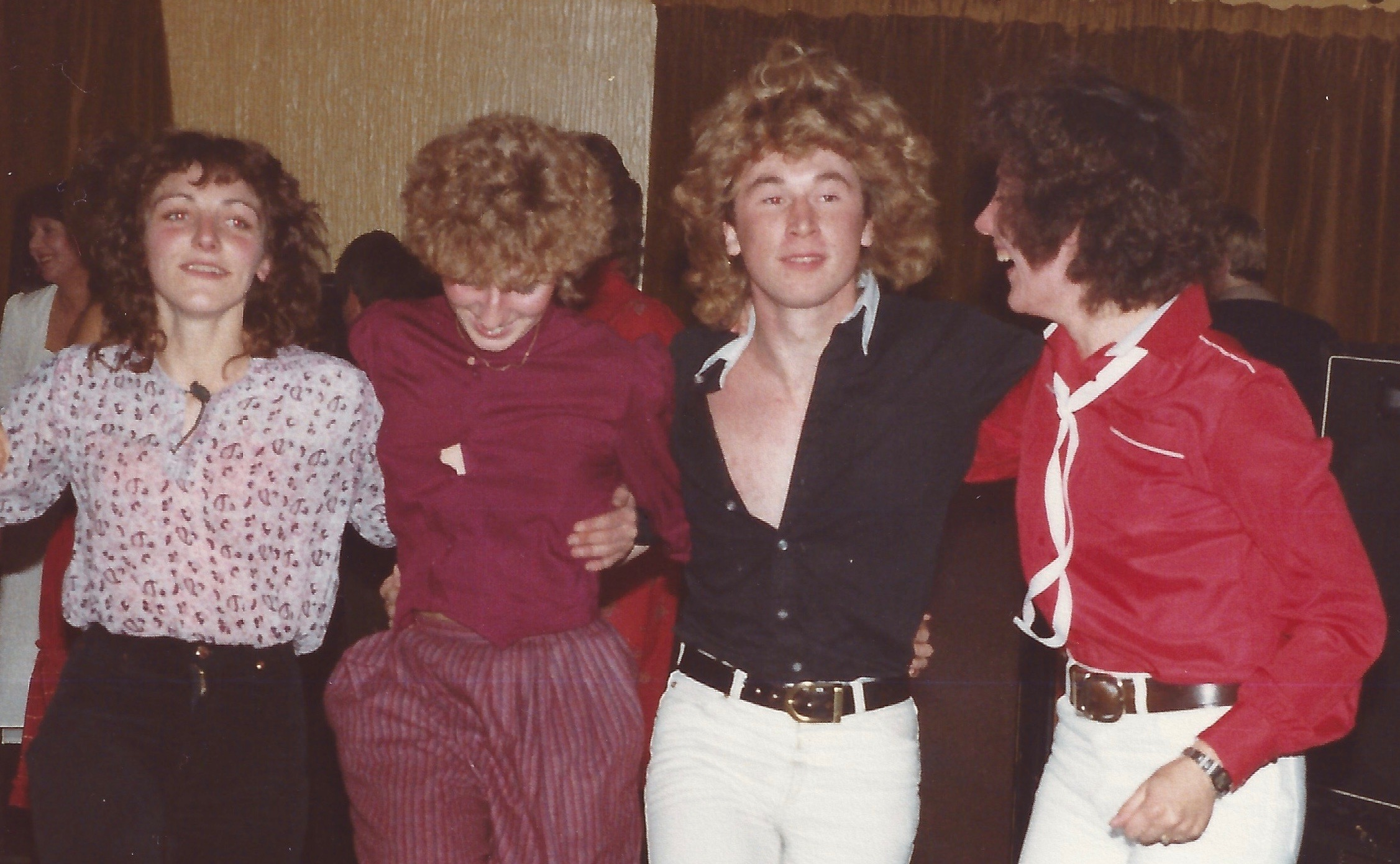 Vince with perm and open shirt dancing with three women