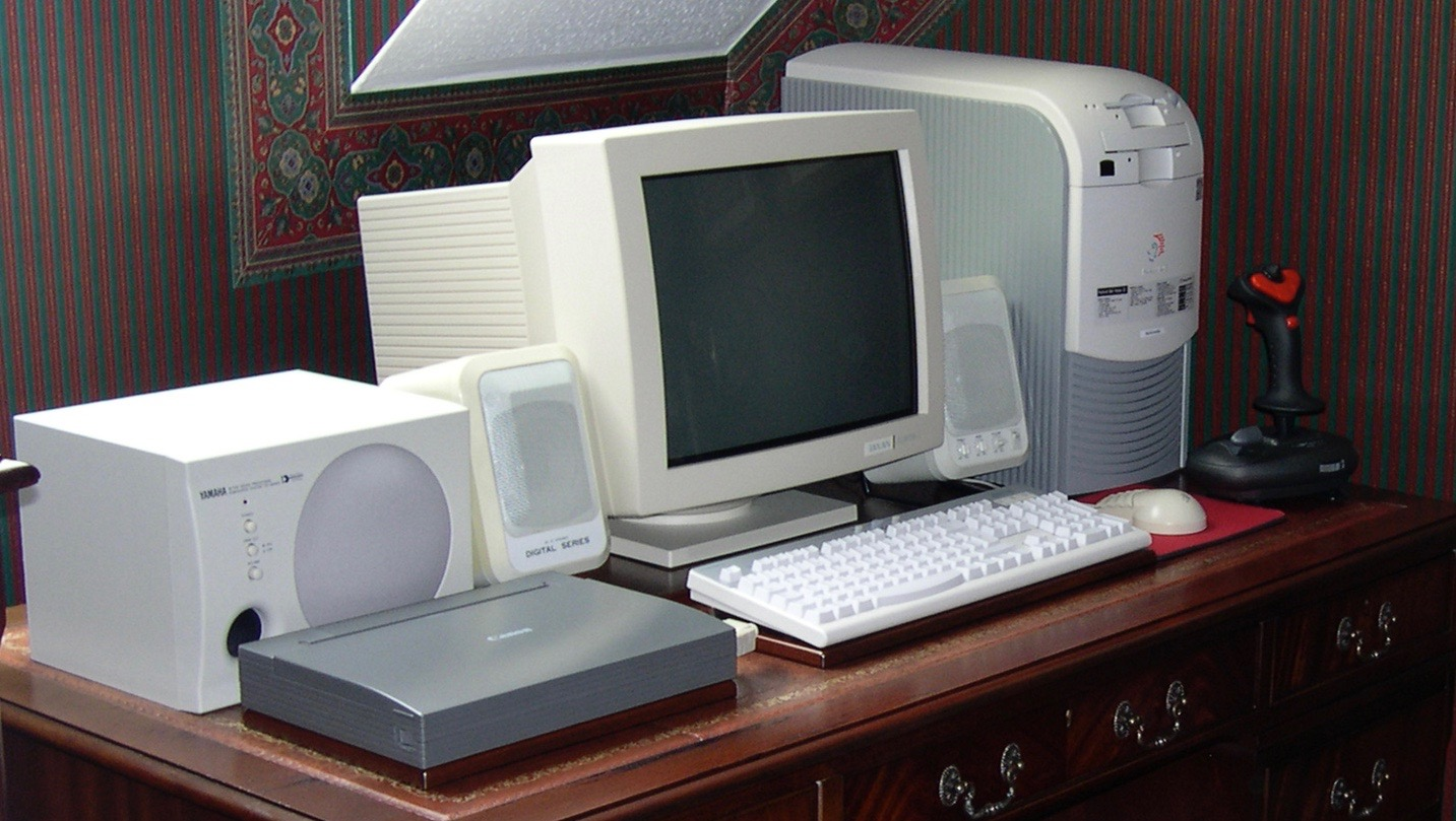 Computer set up on classic desk showing Packard Bell tower case, Taxan CRT monitor, Canon Bubblejet printer, twin speakers and joystick