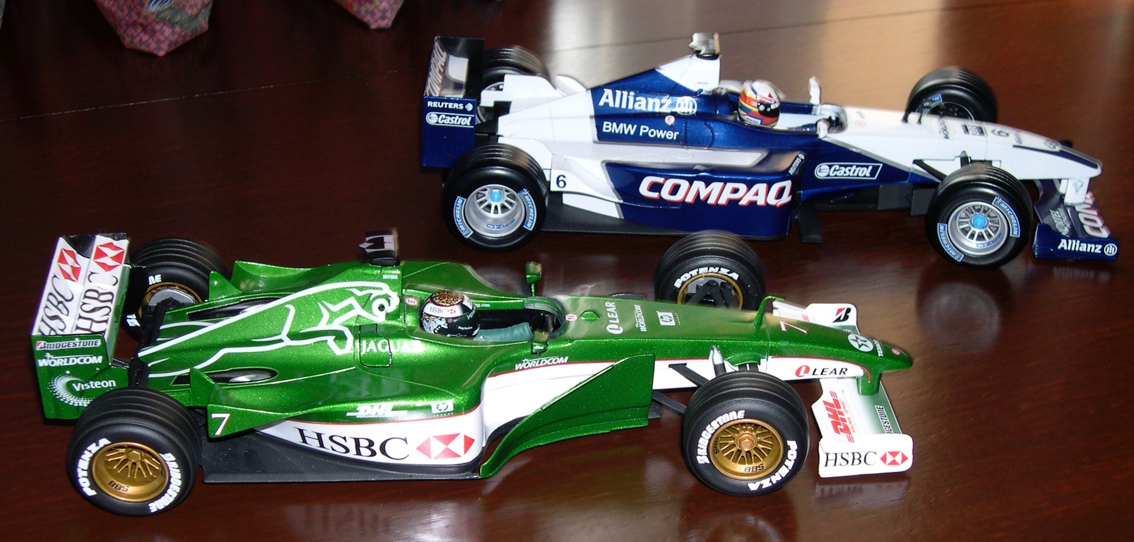 Two detailed colourful model Formula 1 racing cars.  Jaguar Racing and BMW