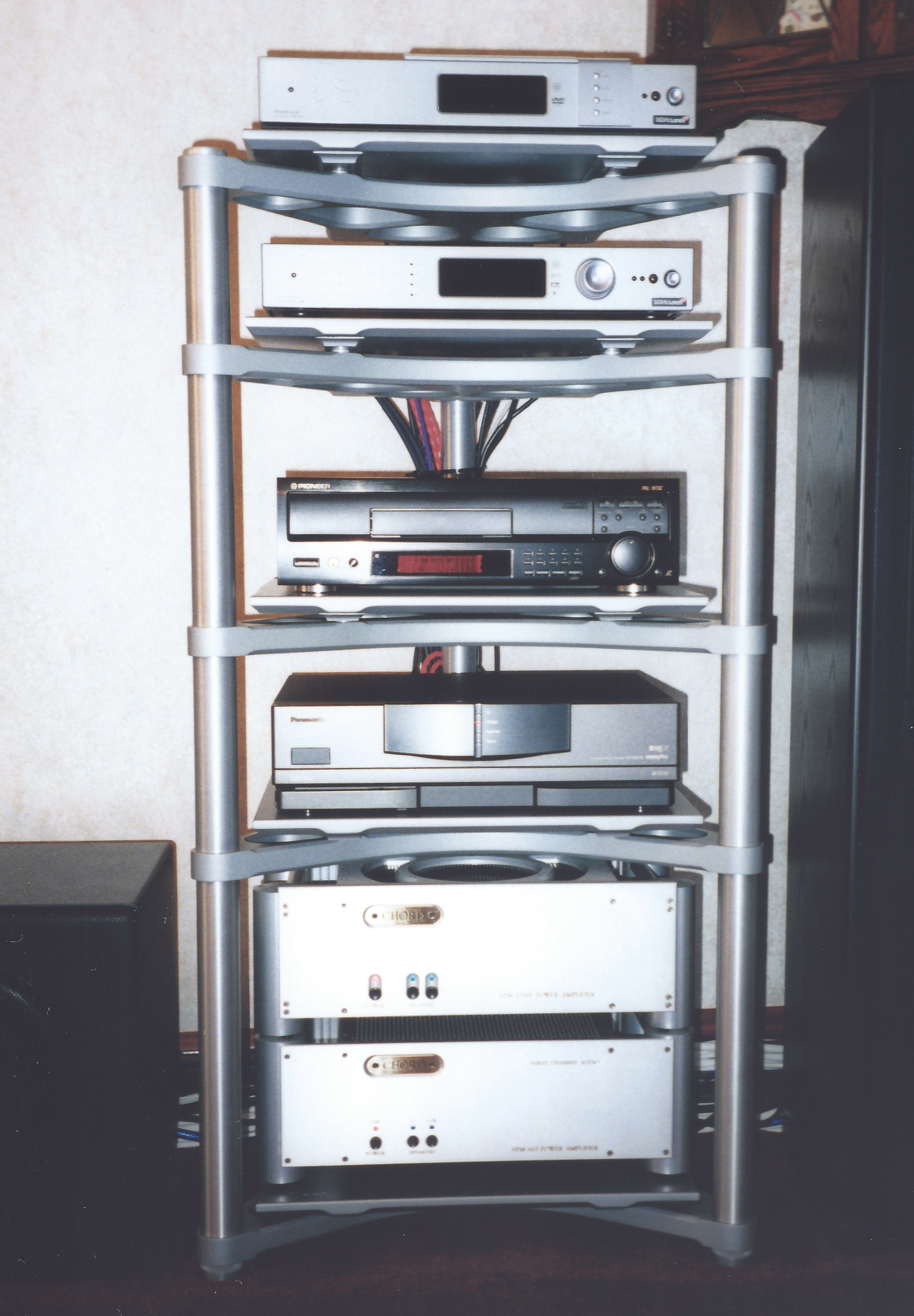 Image of a high end Hi-Fi stack comprising top-loading DVD player, sound processor, laserdisc player, video cassette deck and a pair of power amps on a substantial alloy triangular base stand