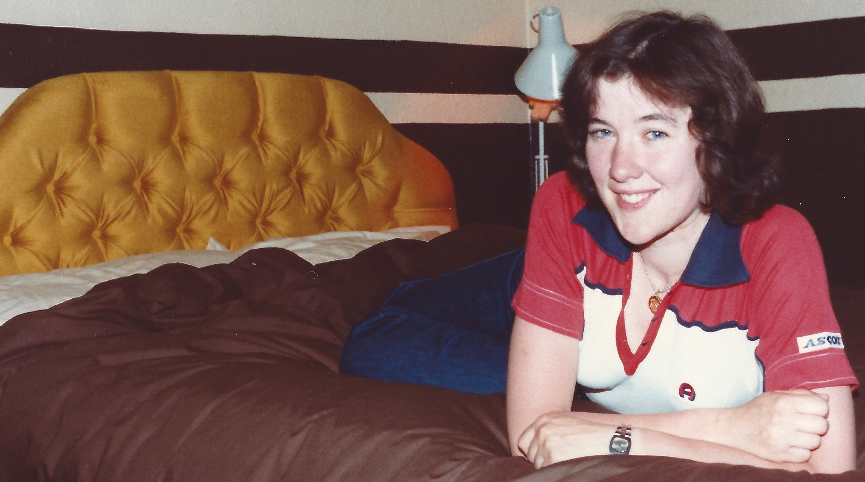 A photograph of Lynda lying prone on top of a bed