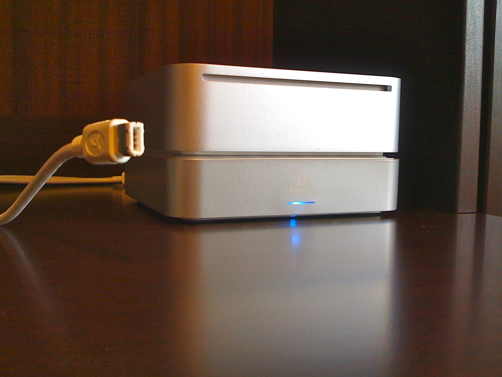 A mac Mini 2 sits on top of a matching Iomega backup hard drive. The associated firewire lead has been removed from an adjacent USB drive but the kink in the cable remains meaning the open Firewire end floats in the air