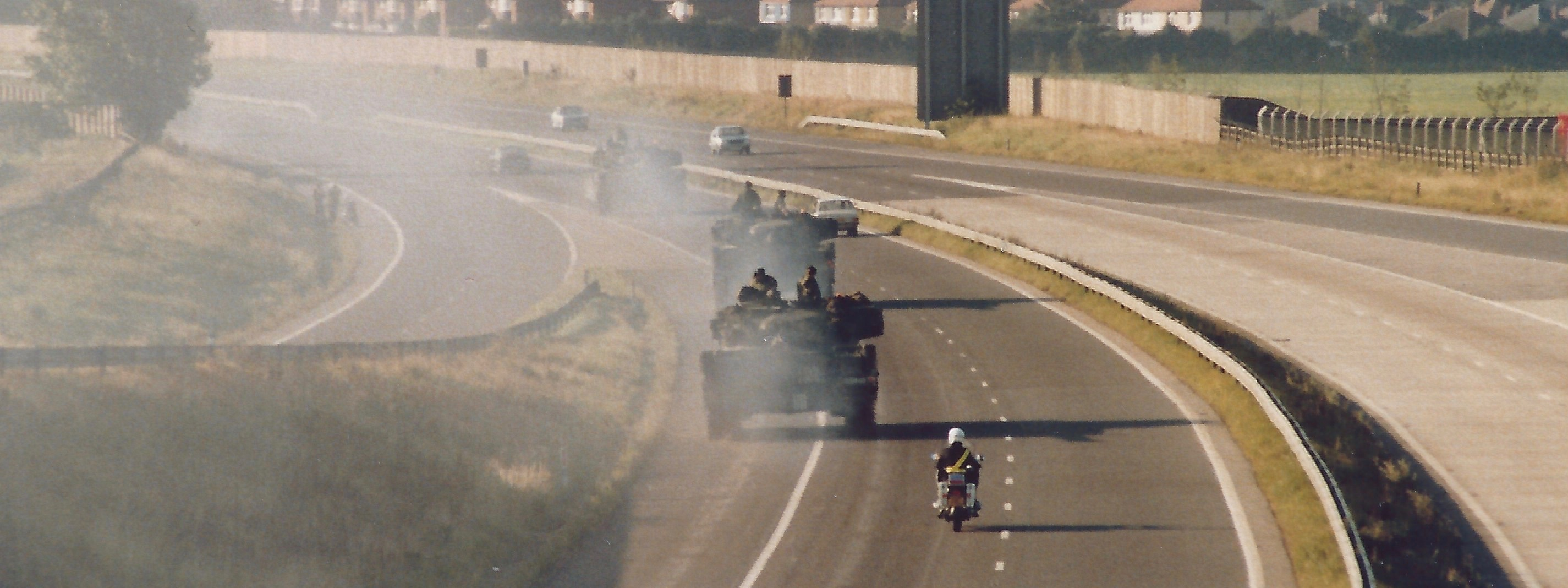 A photograph showing a convoy of tanks heading away on a motorway with a police outrider escort